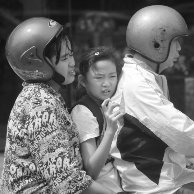 A girl sandwiched atop a scooter.